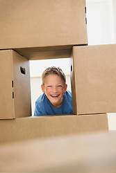 Boy building pile cardboard boxes moving house
