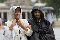 © Licensed to London News Pictures. 30/08/2017. LONDON, UK.  Tourists are caught in heavy rain showers and wet weather near the Tower of London at lunchtime. Heavy rain is forecast to fall across areas of the country today.  Photo credit: Vickie Flores/LNP
