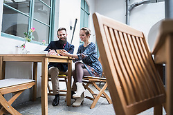 Smiling young couple using mobile phone at cafe