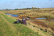 Two people birdwatching in coastal marshland near Shingle Street, Suffolk, England