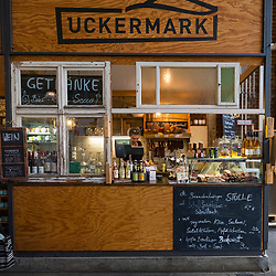 Shop selling wine and bread and deli produce at indoor market , Markethalle Neun, Kreuzberg, Berlin, Germany.