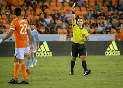 August 4, 2018 - Houston, TX, U.S. - HOUSTON, TX - AUGUST 04:  Houston Dynamo defender Leonardo (22) receives a yellow card from referee Chris Penso for grabbing Sporting Kansas City forward Gianluca Busio (13) during the soccer match between Sporting Kansas City and Houston Dynamo on August 4, 2018 at BBVA Compass Stadium in Houston, Texas.  (Photo by Leslie Plaza Johnson/Icon Sportswire) (Credit Image: © Leslie Plaza Johnson/Icon SMI via ZUMA Press)