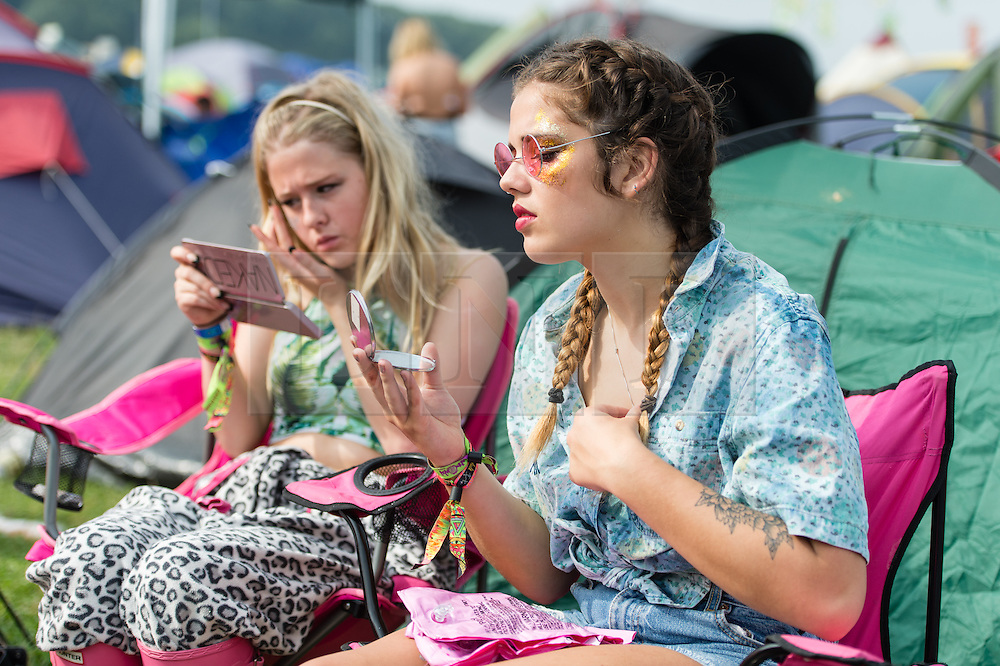 © Licensed to London News Pictures. 06/09/2014. Isle of Wight, UK. A group of young female festival goers at Bestival 2014 Day 3 Saturday spending the morning getting their makeup and outfits ready for the fancy dress day ahead.   Today is the festival's Fancy Dress Day - this year the theme is Desert Island Disco.  Festival goers spend the morning readying their costumes before the judging of the competition at 2pm.  This weekend's headliners include Chic featuring Nile Rodgers, Foals and Outcast.   Bestival is a four-day music festival held at the Robin Hill country park on the Isle of Wight, England. It has been held annually in late summer since 2004.    Photo credit : Richard Isaac/LNP