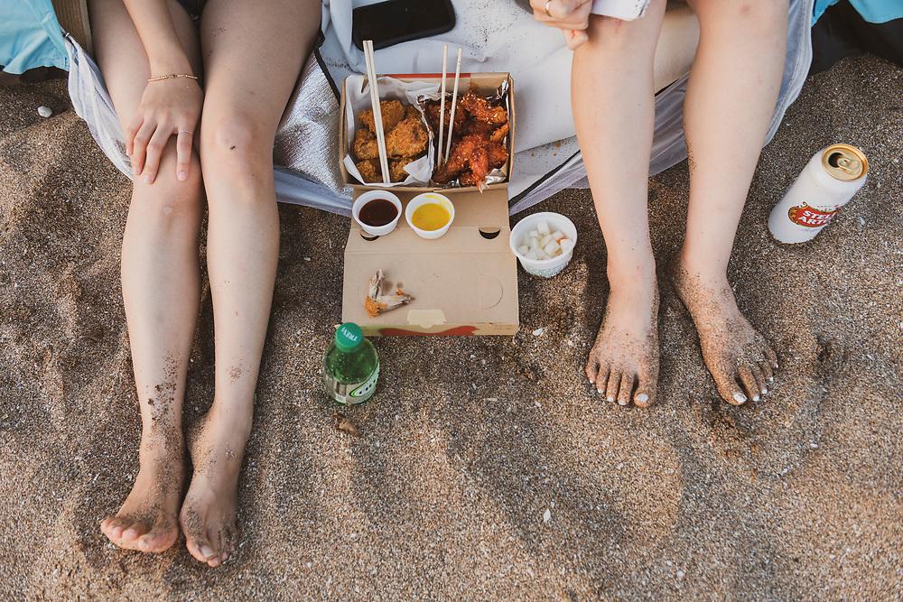 Jeju Island, South Korea - September 15, 2019: Two friends enjoy a meal at Jungmun Beach on Jeju Island, South Korea.