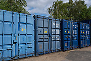 A row of numbered blue metal storage shipping containers in a self-storage depot on 17th June 2019 in Aldershot, Hampshire, United Kingdom.