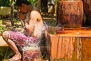 "02 JULY 2013 - ANGKOR WAT, SIEM REAP, SIEM REAP, CAMBODIA:  Water falls around a praying man during a blessing by a Buddhist monk at a small monastery near the Bayon temple in the Angkor Wat complex. Angkor Wat is the largest temple complex in the world. The temple was built by the Khmer King Suryavarman II in the early 12th century in Yasodharapura (present-day Angkor), the capital of the Khmer Empire, as his state temple and eventual mausoleum. Angkor Wat was dedicated to Vishnu. It is the best-preserved temple at the site, and has remained a religious centre since its foundation – first Hindu, then Buddhist. The temple is at the top of the high classical style of Khmer architecture. It is a symbol of Cambodia, appearing on the national flag, and it is the country's prime attraction for visitors. The temple is admired for the architecture, the extensive bas-reliefs, and for the numerous devatas adorning its walls. The modern name, Angkor Wat, means ""Temple City"" or ""City of Temples"" in Khmer; Angkor, meaning ""city"" or ""capital city"", is a vernacular form of the word nokor, which comes from the Sanskrit word nagara. Wat is the Khmer word for ""temple grounds"", derived from the Pali word ""vatta."" Prior to this time the temple was known as Preah Pisnulok, after the posthumous title of its founder. It is also the name of complex of temples, which includes Bayon and Preah Khan, in the vicinity. It is by far the most visited tourist attraction in Cambodia. More than half of all tourists to Cambodia visit Angkor.         PHOTO BY JACK KURTZ"