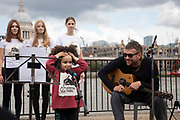 Art work by Ackroyd & Harvey made in grass with words by Ben Okri is set to float on the rising tide on the Thames on the 25th of June 2021, Central London, United Kingdom. The message is a call for action to save the planet from climate change catastrophe. Damian Albarn sings with Mirabella Okris and the Capital Choir. The art work was moved by activists and laid onto a raft on the Thames as the tide was rising. The event marks the launch of XR Writers Rebel's Paint the Land project, which teams acclaimed writers and artists to create landscape graffitos drawing attention to the climate and ecological emergency. The Speakers at the event included the artist Ackroyd & Harvey, writer Ben Okri, Kelly Hill and Simon Bramwell, co-founder of Extinction Rebellion.  The event finished with a song by Damon Albarn and Mirabella Okra and the Capital Choir.