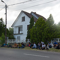 Illegal migrants from Afghanistan and Africa sit on the road side waiting for police to arrive in border town Asotthalom (about 190 km South-East of capital city Budapest), Hungary on July 16, 2015. ATTILA VOLGYI