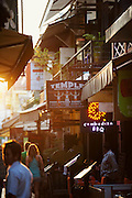 Toursits walk down a street cluttered with restaurants in Siem Reap, Cambodia