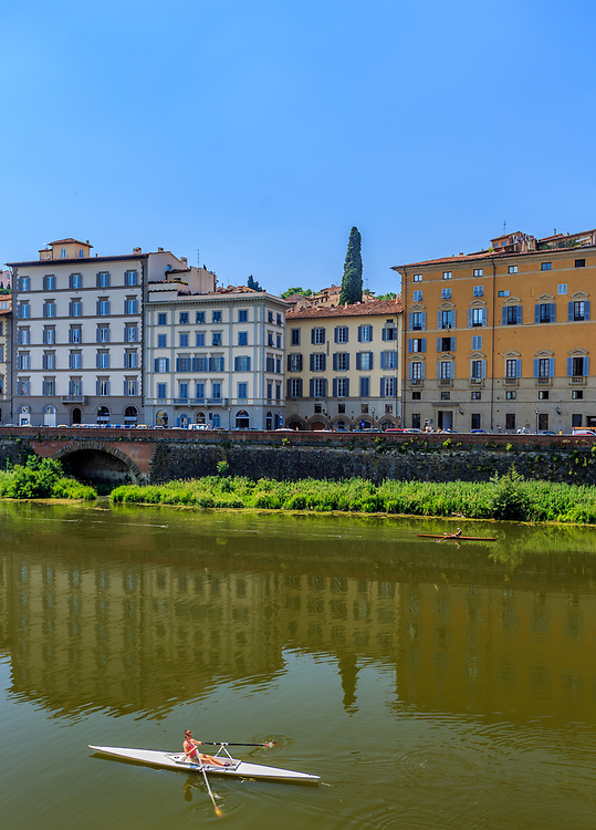 People are kayaking on the Arno river in Florence, Italy.