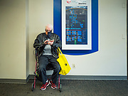 15 MAY 2020 - DES MOINES, IOWA: A man wearing a face mask checks his smart phone while he sits in the Skywalk in downtown Des Moines. The Governor of Iowa allowed most businesses in Iowa to reopen today, including restaurants, barbershops, coffee shops and malls. Restaurants are supposed to be working at 50% of normal capacity and barbershops are urged to take reservations and not allow customers to wait in the shop.  Movie theaters, bars, museums, zoos, and casinons are still closed. On Friday, 15 May, Iowa reported 14,049 cases of COVID-19 and 336 deaths from disease since the start of the pandemic. Iowa's total number of infections continue to rise and several communities in Iowa have emerged as national hotspots for the spread of Coronavirus (SARS-CoV-2).           PHOTO BY JACK KURTZ