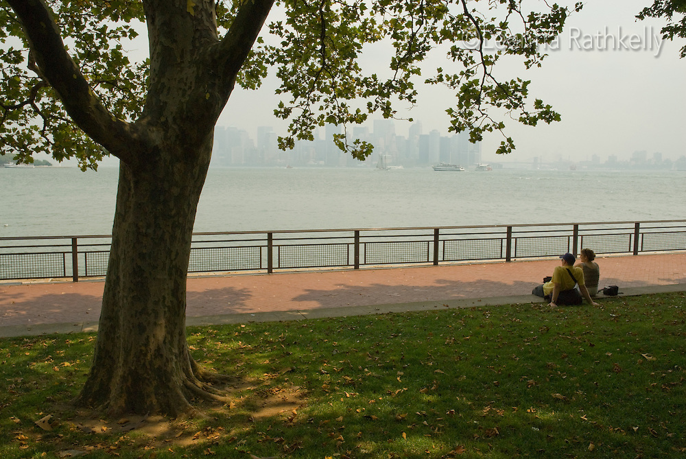 A couple relax under a tree while they look to the Manhattan skyline,  New York City, from Liberty Island.
