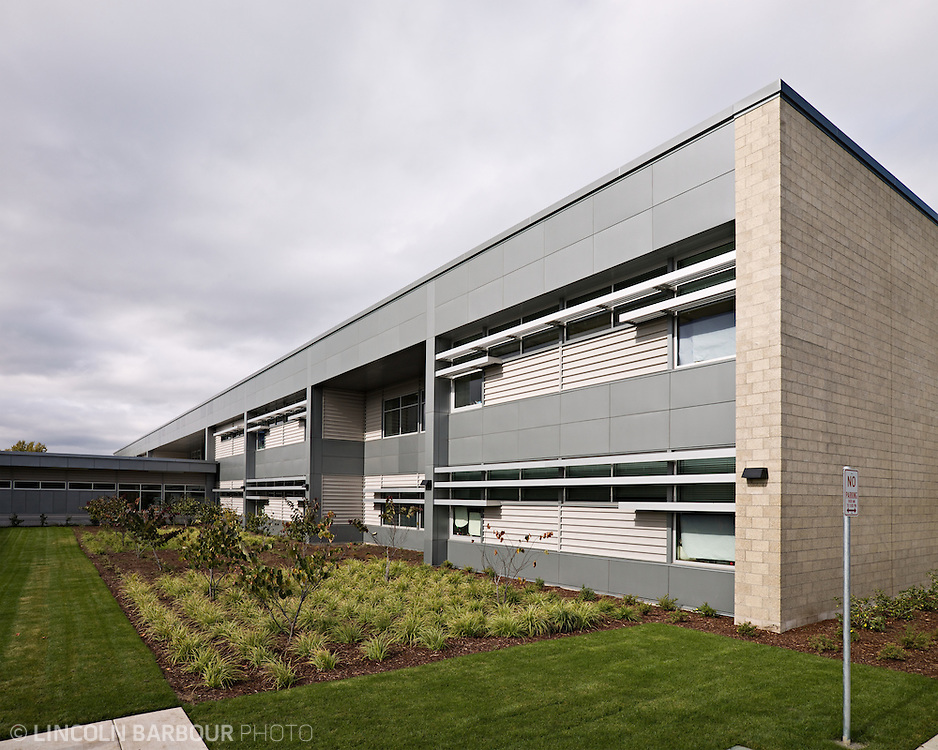 An exterior of a large building with metal and brick facade.  It's an overcast day.  The building is angled away from the camera to the left, making lots of good lines.