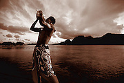 A man, native to Tahiti, blows into a conch shell on the beach