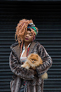A young woman with her pet Pomeranian dog in Brixton on the 11th April 2018 in South London, United Kingdom.