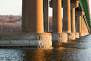Early winter Mississippi River evening, the water flows calmly under a massive bridge.