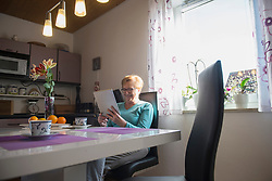 Happy old woman watching digital tablet at breakfast table