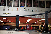 UFC flyweight Sergio Pettis looks on while his older brother UFC featherweight Anthony Pettis of Wisconsin hits mitts with striking coach Brandon Gibson at Jackson Wink MMA in Albuquerque, New Mexico on June 9, 2016.