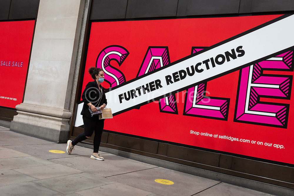 On the day that covid pandemic guidelines for shoppers in England mean that the wearing of face coverings in shops is mandatory, shoppers walk past Sales windows of Seflridges on Oxford Street in the capitals West End, on 24th July 2020, in London, England.