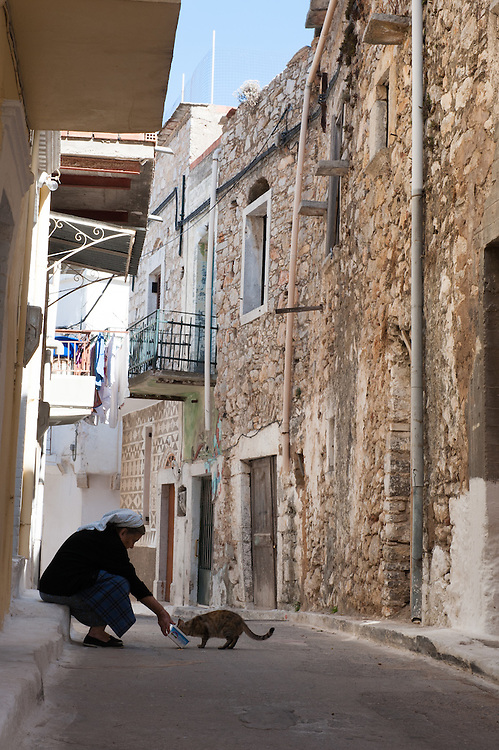 """An old woman feeding a cat in an alley in the medieval village of Pyrgi, Chios, Greece.<br /> <br /> Pyrgi in Chios is known as the """"painted village"""" on account of the decoration of the houses. The village still keeps its medieval style and together with the other Mastichochoria (Mastic Villages) are in the list of the Intangible Cultural Heritage of Humanity of UNESCO"""