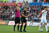 Dwight Gayle of Newcastle Utd gets a yellow card off referee Mike Jones. Premier league match, Swansea city v Newcastle Utd at the Liberty Stadium in Swansea, South Wales on Sunday 10th September 2017.<br /> pic by  Andrew Orchard, Andrew Orchard sports photography.