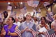 """04 JULY 2009 -- PHOENIX, AZ:  New US citizens wave their flags at a naturalization ceremony in Phoenix, AZ, July 4. U.S. Citizenship and Immigration Services and South Mountain Community College in Phoenix, AZ, hosted the 21st annual """"Fiesta of Independence"""" Saturday, July 4. More than 180 people from 58 countries took the US Oath of Citizenship and became naturalized US citizens. The ceremony was one of dozens of similar ceremonies held across the US this week. USCIS said more than 6,000 people were naturalized US citizens during the week.  Photo by Jack Kurtz / ZUMA Press"""