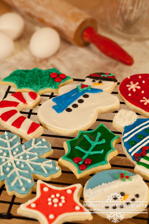 Variety of decorated Christmas sugar cookies with measuring cup and fresh eggs in the background.