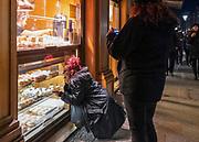 2020-02-08 Kraków, ul. Grodzka. Kobieta oglądająca witrynę wystawową cukierni.