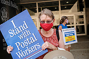 25 AUGUST 2020 - DES MOINES, IOWA: REBECCA HOEPPNER, from Ames, IA, participates in a rally in support of the USPS at the Neal Smith Federal Building in Des Moines. About 100 people, postal workers and members of the public, came to the Neal Smith Federal Building Tuesday to call for increased spending for the US Postal Service and an end to attacks on the USPS by members of the Trump administration. The rally was a part of a series national rallies organized by the American Postal Workers Union (APWU). Many of the people at the rally expressed concerns that the President's actions versus the USPS could harm their ability vote by mail in the November general election.      PHOTO BY JACK KURTZ