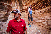 SHOT 10/15/16 1:03:18 PM - Doug Starkey (left) of Steamboat Springs, Co. and Mike Tryggestad of Denver, Co. explore a slot canyon along the White Rim Trail. The White Rim is a mountain biking trip in Canyonlands National Park just outside of Moab, Utah. The White Rim Road is a 71.2-mile-long unpaved four-wheel drive road that traverses the top of the White Rim Sandstone formation below the Island in the Sky mesa of Canyonlands National Park in southern Utah in the United States. The road was constructed in the 1950s by the Atomic Energy Commission to provide access for individual prospectors intent on mining uranium deposits for use in nuclear weapons production during the Cold War. Four-wheel drive vehicles and mountain bikes are the most common modes of transport though horseback riding and hiking are also permitted.<br /> (Photo by Marc Piscotty / © 2016)