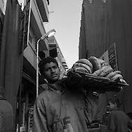 Egypt. Cairo : bread sellers, street life in Gamaliyya area in front of the Khanqah of Sultan Baybars al Gashankir and minaret   Islamic Cairo .NM32