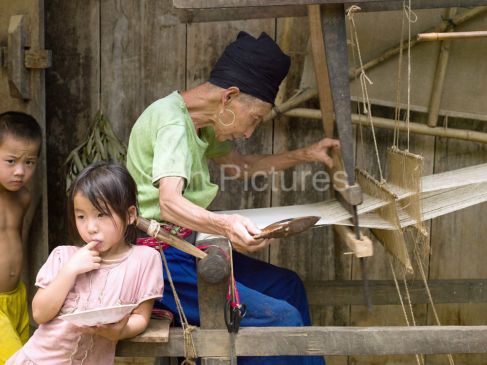 An elderly Hmong woman weaving hemp outside her home in Ban Tatong, Phongsaly province, Lao PDR. Making hemp fabric is a long and laborious process; the end result is a strong durable cloth with qualities similar to linen which the Hmong women use to make their traditional clothing. In Lao PDR, hemp is now only cultivated in remote mountainous areas of the north. The remote and roadless village of Ban Tatong is situated along the Nam Kang river (an offshoot of the Nam Ou) and will be relocated due to the construction of the Nam Ou Cascade Hydropower Project Dam 7.