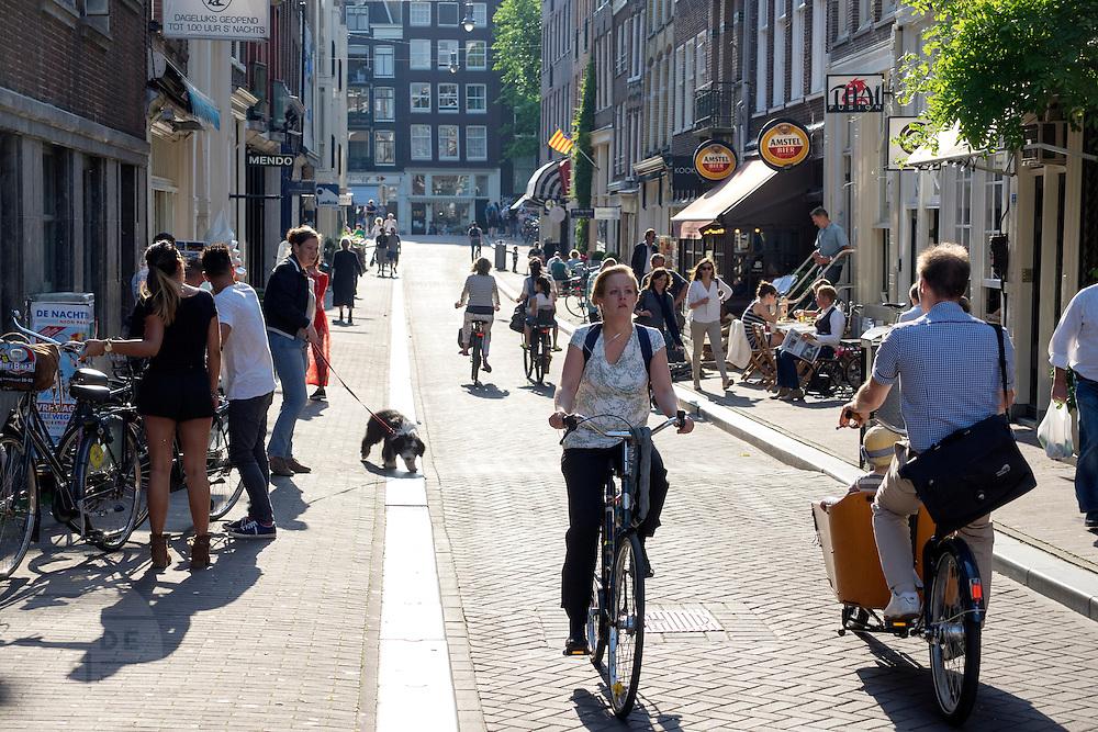 In Amsterdam fietsen mensen door de binnenstad.<br /> <br /> People cycling downtown Amsterdam.