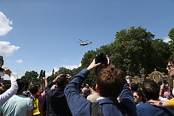 Tourists look on as Marine One arrives at Buckingham Palace, London, during the first day of a state visit to the UK by US President Donald Trump.