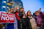 """SAN FRANCISCO, CA - DECEMBER 17: Carter Fields (L) and his wife Julia Bridgeman Fields of San Francisco, California recite the Pledge of Allegiance with their young children who they wished not to be identified, aged 7, 5, and 5, respectively, during demonstrations in part of a national impeachment rally, at the San Francisco Federal Building in San Francisco, California on December 17, 2019. Protesters around the nation participated in """"Nobody is Above the Law"""" rallies on the eve of a historic Trump impeachment vote in the United States House of Representatives. The crowd size at the San Francisco event is approximated in the several hundreds. (Photo by Philip Pacheco/AFP)"""