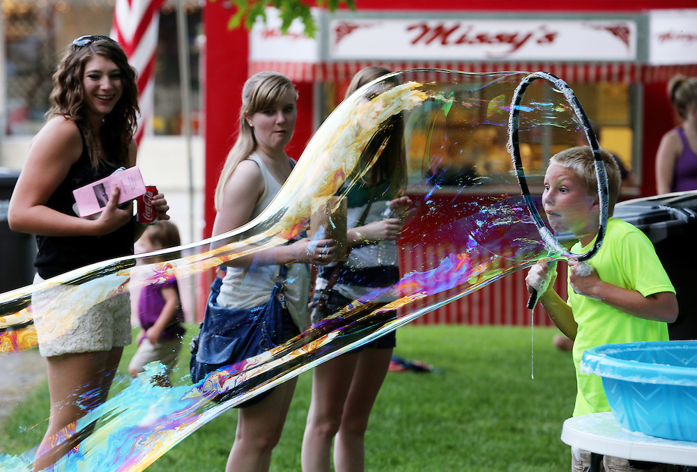 Much to his enjoyment, Wade Ohlson, 8, of Aurora, makes a large bubble during the A'ror'n Days festival Thursday at the courthouse square in Auora. (Independent/Matt Dixon)