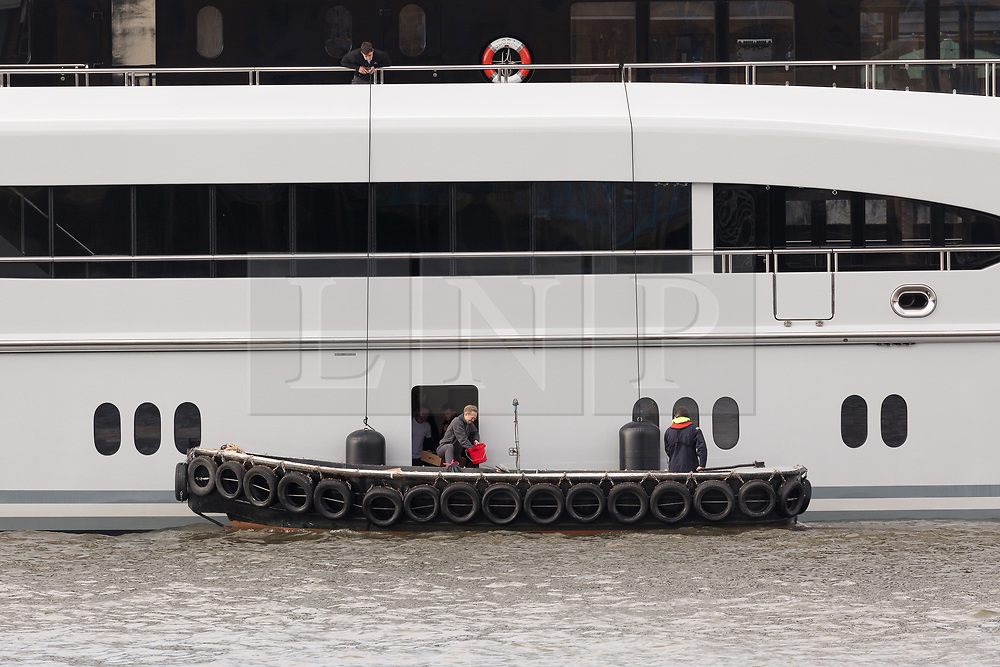 © Licensed to London News Pictures. 29/03/2018. London, UK. People working with a support boat to the 220ft custom luxury superyacht, 'Global' moored at Butlers Wharf near Tower Bridge during a London visit. Previously named, Kismet during her last central London visit, she underwent a refit which saw her moved up 51 places in Boat International's list of top 200 largest super yachts in the world, boasting numerous luxuries such as a helipad, cinema and jacuzzi. Believed to be owned by Fulham Football Club chairman, Shahid Khan, Global can be chartered for an estimated £1m per week. Powered by 2 Caterpillar (3512 B) 2,038hp diesel engines and propelled by her twin screws propellers, Global is capable of a top speed of 15.5 knots, and comfortably cruises at 14 knots.. Photo credit: Vickie Flores/LNP