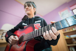 18 February 2020, Amman, Jordan: Fourteen-year-old Shahed plays the guitar in the Talent Room of Rufaida Al Aslamieh Primary Mixed School in the Sahab district. The school serves more than 1,000 students from kindergarten up to 10th grade, most of them girls from Jordan but also some from Syria and other countries, and, in the lower grades, also boys. With support from the Lutheran World Federation, the school has refurbished its rooms and buildings and introduced a 'Talent Room' in order to nurture the children's creativity. This type of learning environment is otherwise rare in Jordanian public shools.