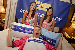 © licensed to London News Pictures. London, UK 18/04/2012. CEO of Ryanair Michael O'Leary (centre) posing with Ryanair cabin crew Carla Dominguez (left) and Ornella Matrisciano (right) to promote the launch of ryanairhotels.com, a hotel comparison website, at the Rubens Hotel in London.  Photo credit: Tolga Akmen/LNP
