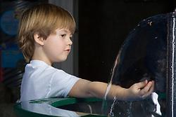 United States, Washington, Bellevue, KidsQuest Children's Museum, boy exploring water at Waterways exhibit