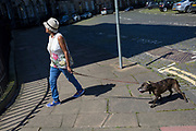 A lady leads her dog while on a summer's walk through Moray Place, on 26th June 2019, in Edinburgh, Scotland.