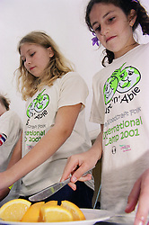 Children assisting with the preparation of food during environmental awareness camp,