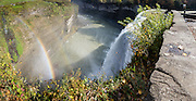 """Middle Genesee Falls rainbow, Portage Canyon, Letchworth State Park, Portageville, New York, USA. In Letchworth State Park, renowned as the """"Grand Canyon of the East,"""" the Genesee River roars northeast through a gorge over three major waterfalls between cliffs as high as 550 feet, surrounded by diverse forests which turn bright fall colors in the last three weeks of October. The large park stretches 17 miles between Portageville and Mount Morris in the state of New York, USA. Drive or hike to many scenic viewpoints along the west side of the gorge. The best walk is along Gorge Trail #1 above Portage Canyon from Lower Genesee Falls (70 ft high), to Inspiration Point, to Middle Genesee Falls (tallest, 107 ft), to Upper Genesee Falls (70 ft high). High above Upper Falls is the railroad trestle of Portageville Bridge, built in 1875, to be replaced 2015-2016. Geologic history: in the Devonian Period (360 to 420 million years ago), sediments from the ancestral Appalachian mountains eroded into an ancient inland sea and became the bedrock (mostly shales with some layers of limestone and sandstone plus marine fossils) now exposed in the gorge. Genesee River Gorge is very young, as it was cut after the last continental glacier diverted the river only 10,000 years ago. The native Seneca people were largely forced out after the American Revolutionary War, as they had been allies of the defeated British. Letchworth's huge campground has 270 generously-spaced electric sites. The panorama was stitched from 7 overlapping photos."""