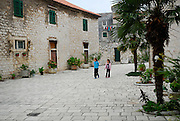 Two children (9 years old, 5 years old) wander through paved street, Sibenik, Croatia