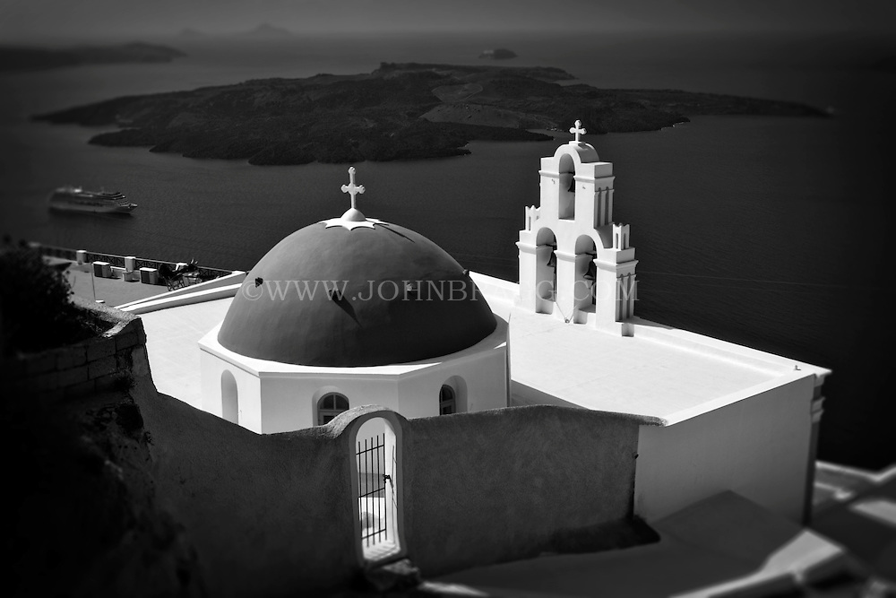 Black and white photo of a church with a domed roof and a view of the Aegean Sea at Santorini, Greece