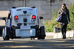 © London News Pictures. 11/10/2016. Milton Keynes, UK. A woman walks past a driverless car being tested Around pedestrian areas in Milton Keynes in the first public test of autonomous electric vehicles in the UK. The vehicles have been developed by the Oxford Robotics Institute and Oxbotica. Photo credit: Ben Cawthra/LNP