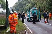Enforcement agents from the National Eviction Team NET, working alongside Thames Valley Police officers, escort a cherry picker as they commence works to evict environmental activists opposed to the HS2 high-speed rail link from Wendover Active Resistance WAR camp on 10th October 2021 in Wendover, United Kingdom. WAR camp, which contains tree houses, tunnels, a cage and a 15-metre tower, is currently the largest of the protest camps set up by Stop HS2 activists along HS2s Phase 1 route between London and Birmingham.