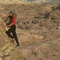 Lisa Gnade climbs on sandstone crags above ancient Nabatean ruins at Petra, Jordan.