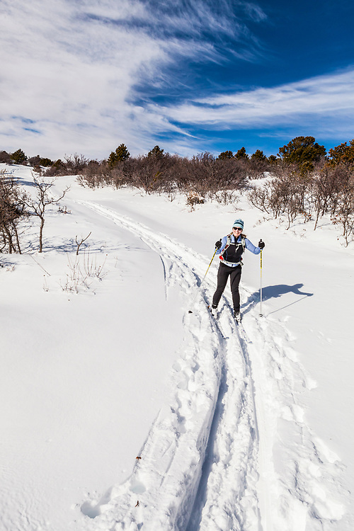 A middle aged woman cross country skiing in the foothills of the La Sal Mountains in southeast Utah, USA.