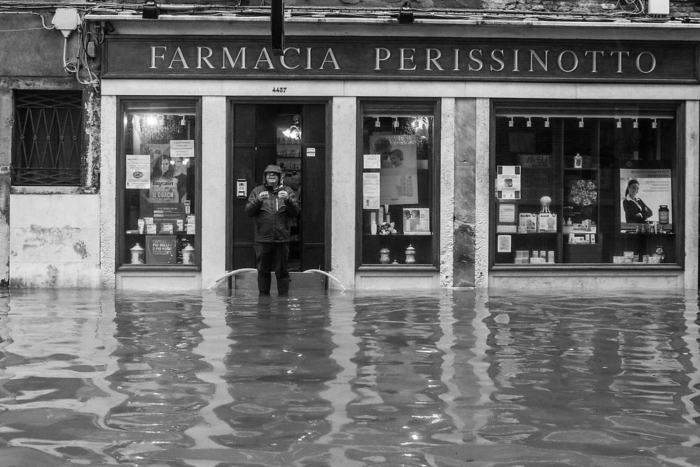 Venice, Italy. 29 October, 2018.  A man stands outside his pharmacy that is flooded while pumping out the water on October 29, 2018, in Venice, Italy. This is a selection of pictures of different areas of Venice that the press has not covered, were resident live and every year they have to struggle with the high tide. Due to the exceptional level of the 'acqua alta' or 'High Tide' that reached 156 cm today, Venetian schools and hospitals were closed by the authorities, and citizens were advised against leaving their homes. This level of High Tide has been reached in 1979. © Simone Padovani / Awakening / Alamy Live News